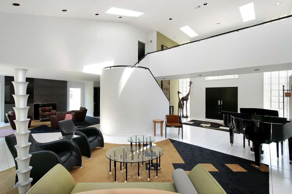 Modern living room with a pair of black chairs and two glass top center tables on top of a stylish brown and black area rug covering the white tiles flooring. There's a black piano set on the side of the space as well.