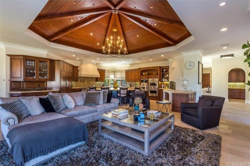 Large living room boasting a stunning tray ceiling with a gorgeous chandelier. The area offers a classy gray sofa set on top of a stylish area rug.