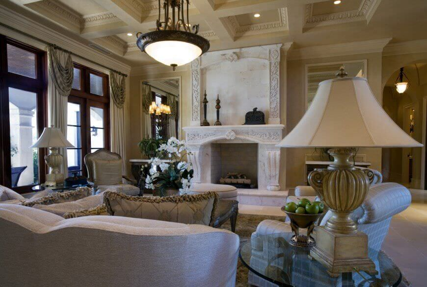 A large formal living room boasting an elegant coffered ceiling and a large fireplace. The room offers luxurious pieces of furniture, lighted by a pendant light and classy table lamps.