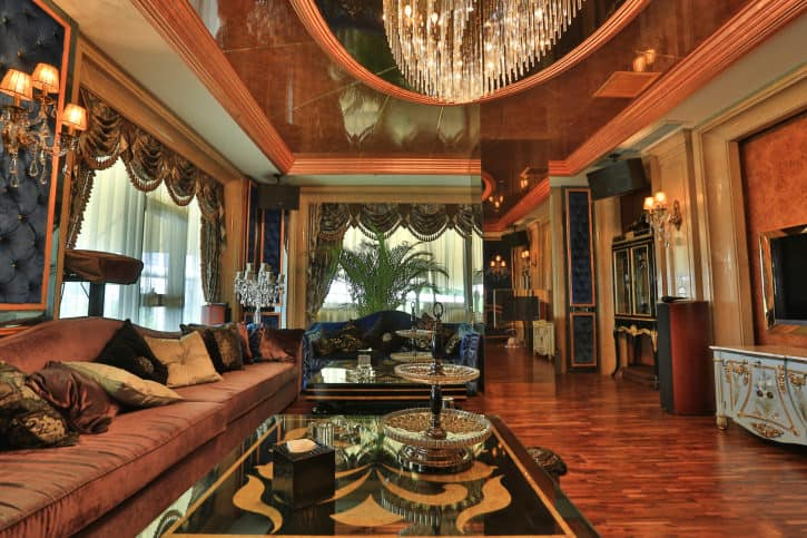 This home boasts a luxurious living space featuring elegant window curtains and a classy sofa set together with stylish center tables lighted by a stunning ceiling light set on a gorgeous ceiling.