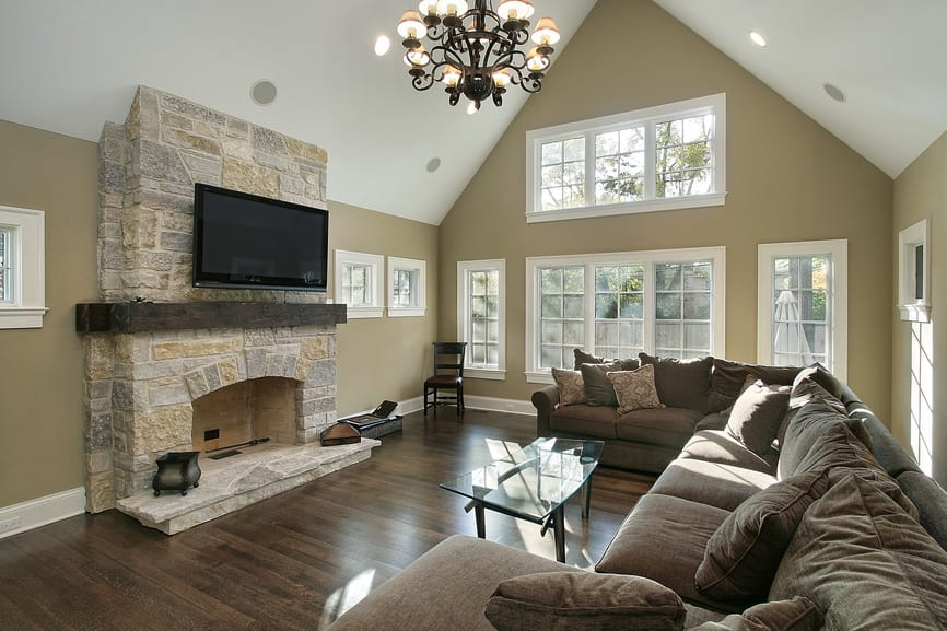 Large living room featuring a large brown and cozy sofa set along with a stylish glass top center table lighted by a gorgeous chandelier. The room also offers a stone fireplace and a widescreen TV above it.