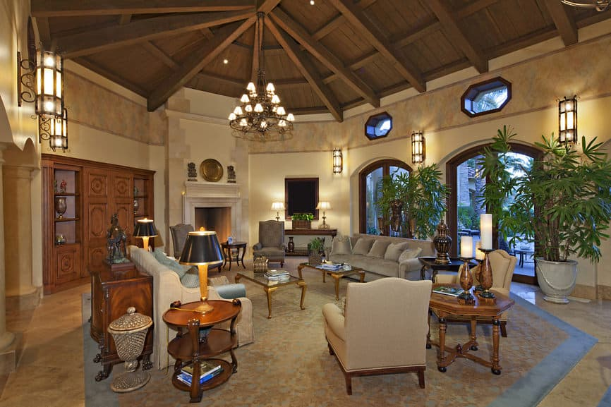 Large formal living room featuring an elegant set of furniture along with a fireplace and a large area rug situated under the home's wooden tall ceiling with exposed beams, lighted by a fancy ceiling light and wall lights.