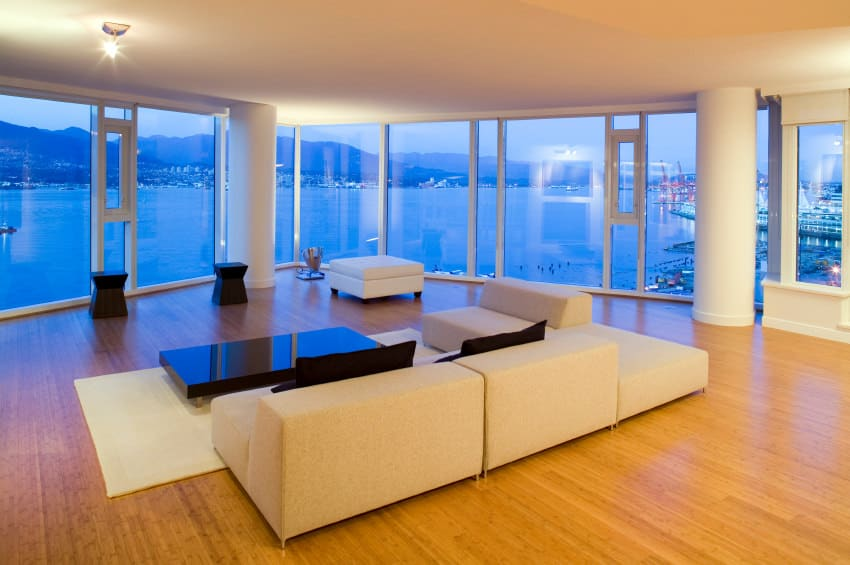 Spacious living room with a modern white sofa set and a stylish center table set on a lovely white area rug. The beautiful outdoor view can be seen from the room through the floor-to-ceiling glass windows.