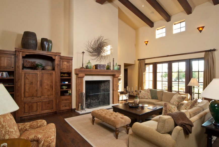Large formal living room featuring hardwood flooring and a tall ceiling with exposed beams. The room offers a set of classy seats, a rustic cabinetry with built-in shelving along with a fireplace.