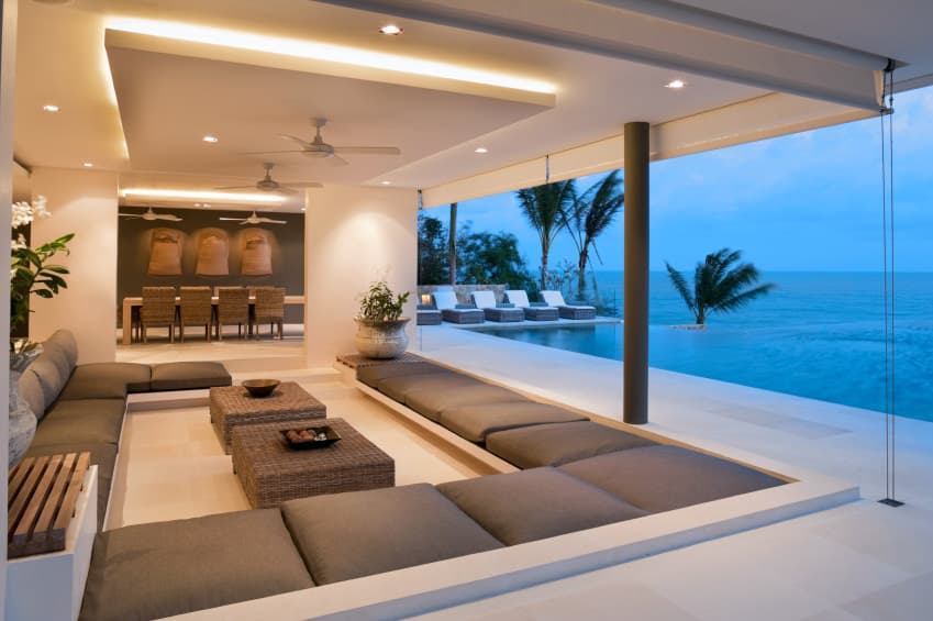 A contemporary home featuring a luxurious living space with a large sofa set and a couple of center tables set to see a breathtaking outdoor view through the home's open windows.