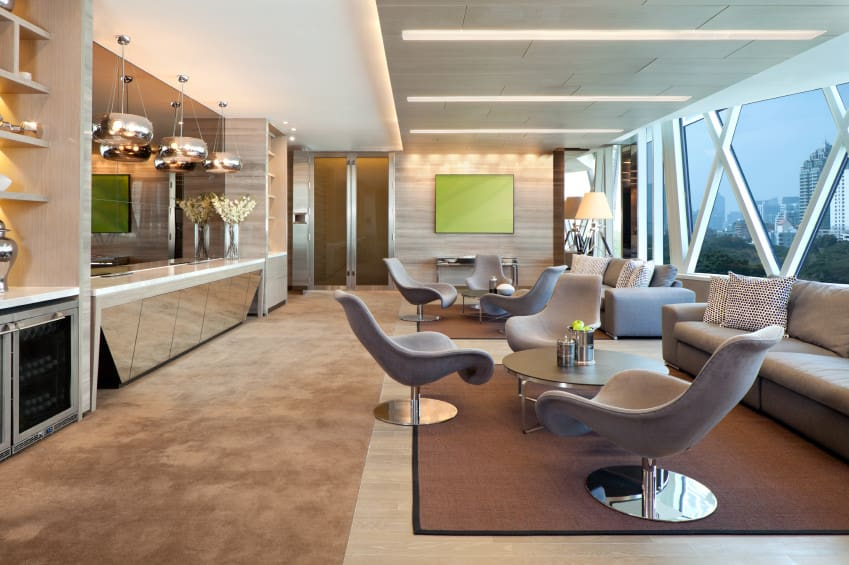 Large living space featuring a set of modern couches and seats, along with a bar area lighted by fancy ceiling lights.