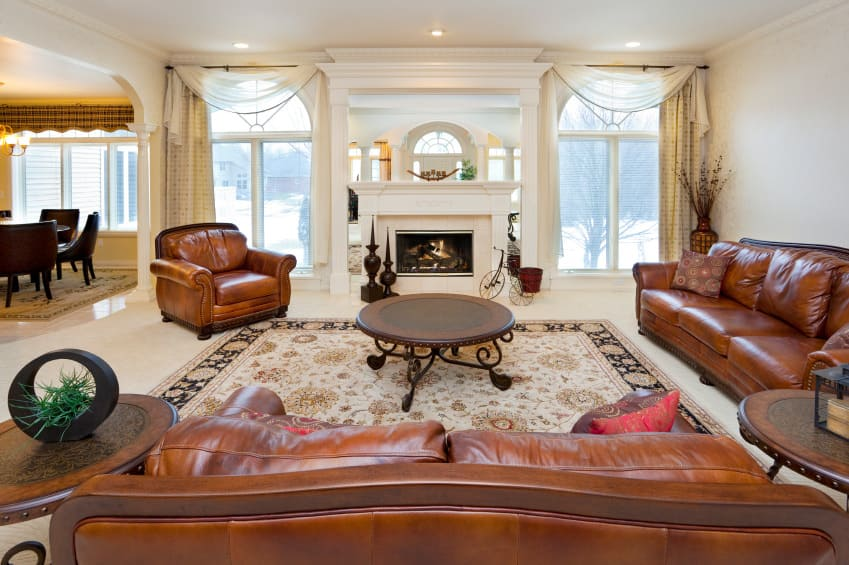 Large formal living room boasting elegant couches and a matching club chair, along with a center table and a fireplace.