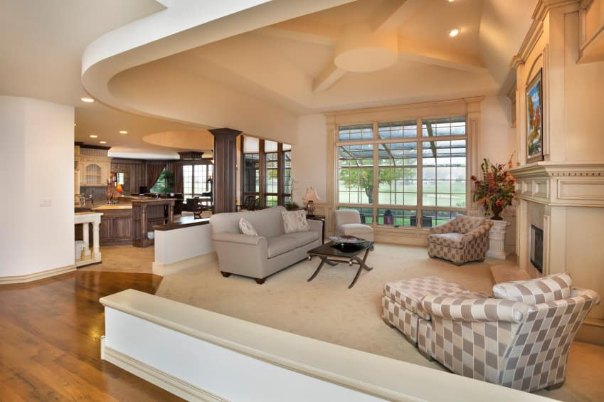 This house features a living space with a custom ceiling and a cozy couch with a center table in front of the fireplace.