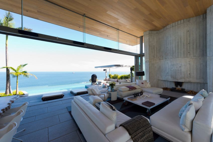 A contemporary home with a spacious living room offering a breathtaking ocean view. The room has a cozy white sofa set along with a white center table and a fireplace.