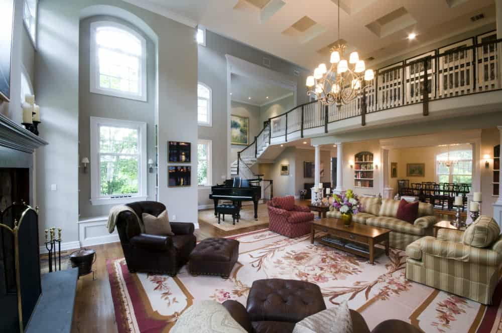 A huge living space under the home's two-storey ceiling. The area has multiple classy seats and a large fireplace, lighted by a gorgeous chandelier.