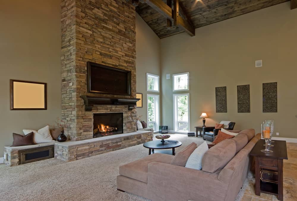 A spacious living room with a cozy sofa set and has a fireplace with a large widescreen TV in front. The area is under the home's rustic tall ceiling.
