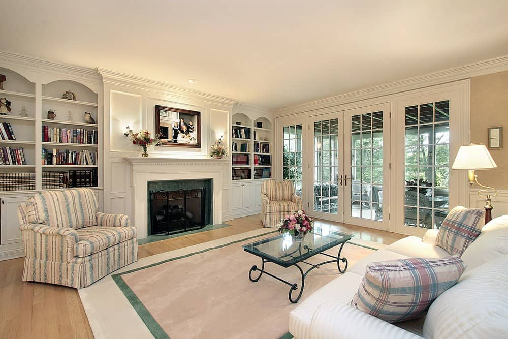 Large formal living space featuring a fireplace in between built-in shelves on both sides, lighted by wall lights.