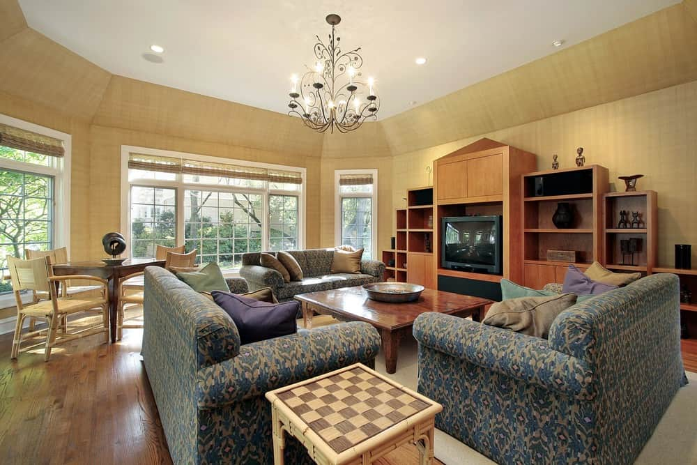 Large living room featuring elegant couches and a large wooden center table on top of an area rug covering the hardwood flooring.