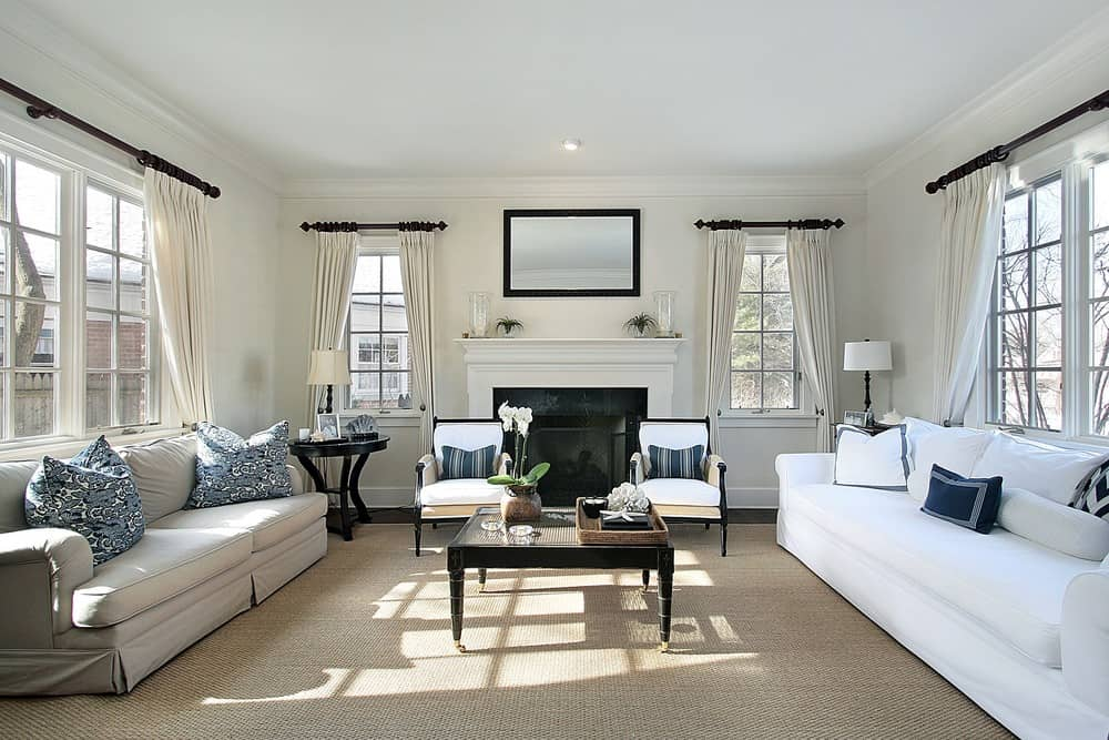 Large living room featuring a white couch and a gray couch. The room has a fireplace and carpeted flooring.