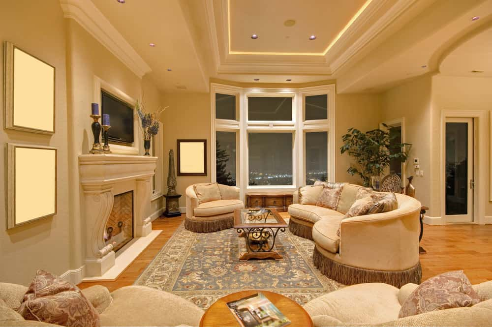 Spacious living room featuring a gorgeous tray ceiling and a classy area rug. The area offers a beautiful sofa set and a large fireplace.