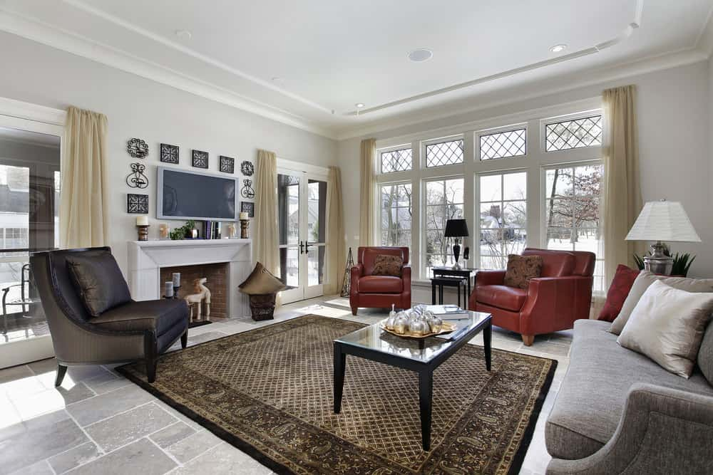 Large living room featuring a set of classy seats, along with a center table set on a stylish brown area rug covering the tiles flooring. The room offers a fireplace and a TV on the wall.