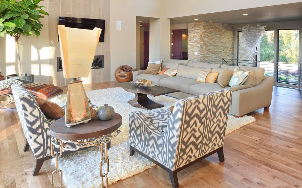 A spacious living room with stylish chairs and a long modern couch, along with a gas fireplace and a widescreen TV in front.