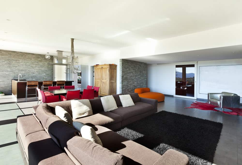 A great room featuring a large living space with a stylish sofa set and an area rug.