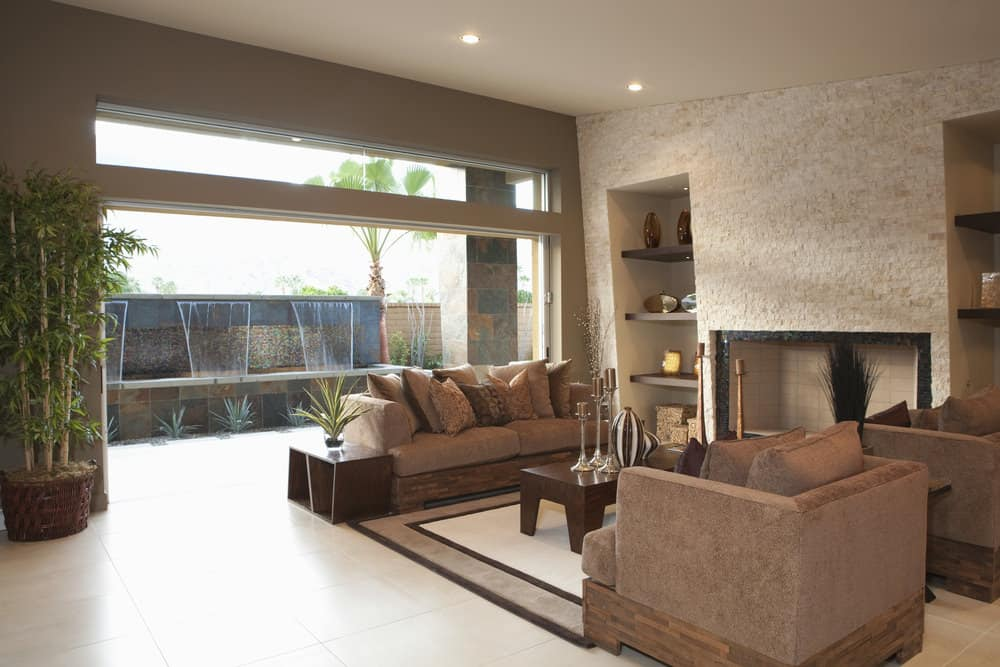 A living room with a set of modern seats and a center table set on top of a stylish area rug.