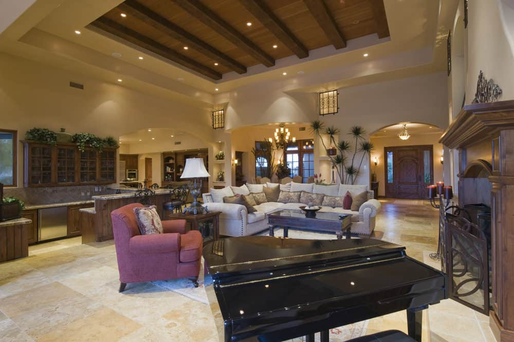 A spacious great room boasting a living space with a classy sofa set and a black piano on the side of the fireplace.