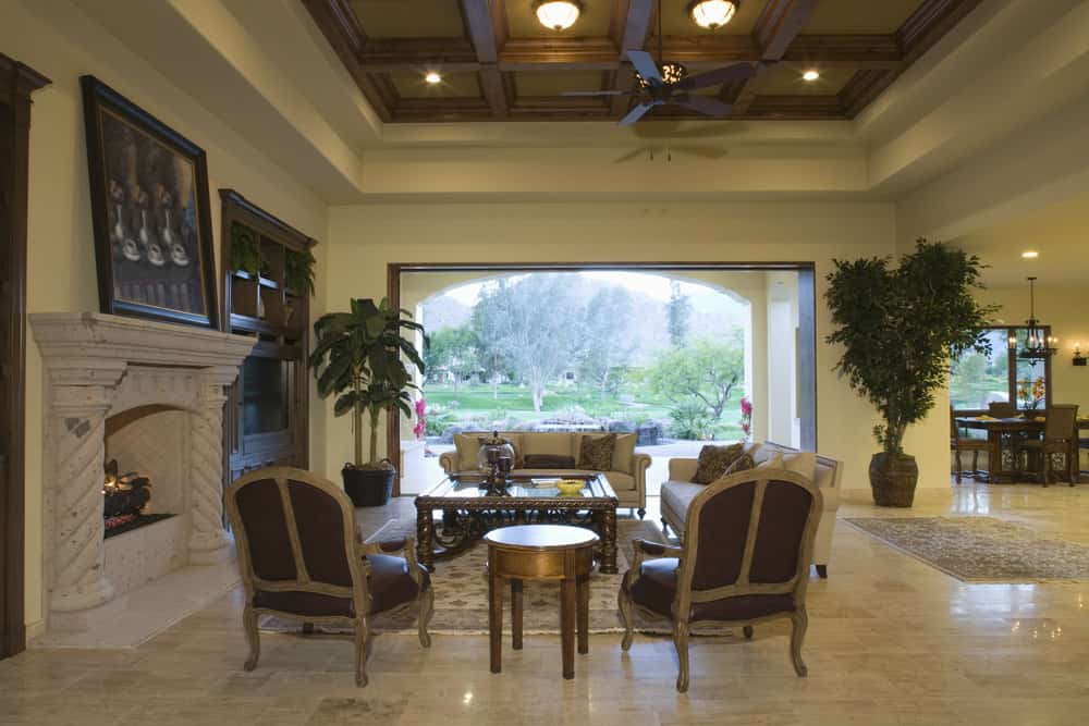 Large living space situated under the home's gorgeous ceiling. The area has a large fireplace and a set of classy furniture.
