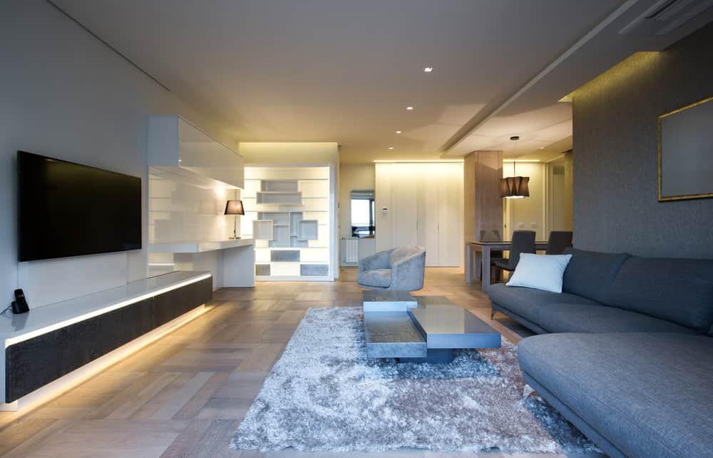 Large contemporary living space featuring a large gray sofa set and a large flat-screen TV on the wall in front of the sofa set.