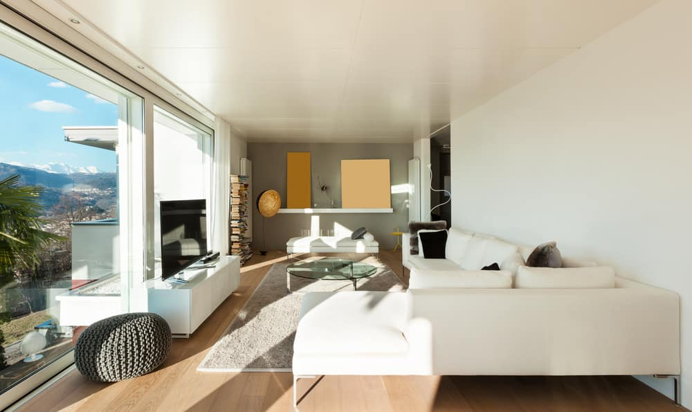 Modern family living room with a large white sofa set and a large flat-screen TV in front. The area has floor-to-ceiling glass windows overlooking the beautiful city too.
