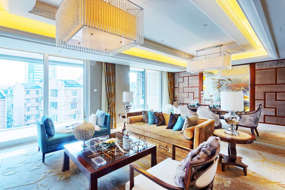 Large and luxurious formal living room under the home's stunning tray ceiling lighted by fancy ceiling lights. The room offers elegant pieces of furniture and beautifully decorated flooring.