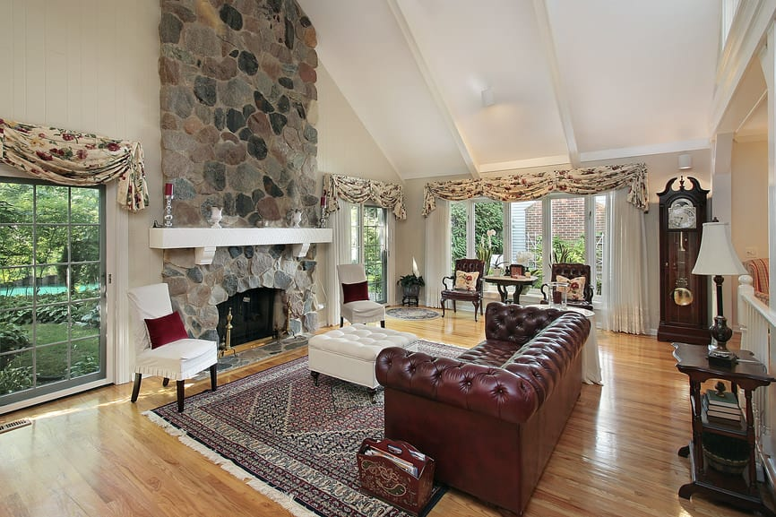 Large formal living room boasting an elegant leather sofa and a large stone fireplace. The room also has elegant seats and other pieces of furniture.