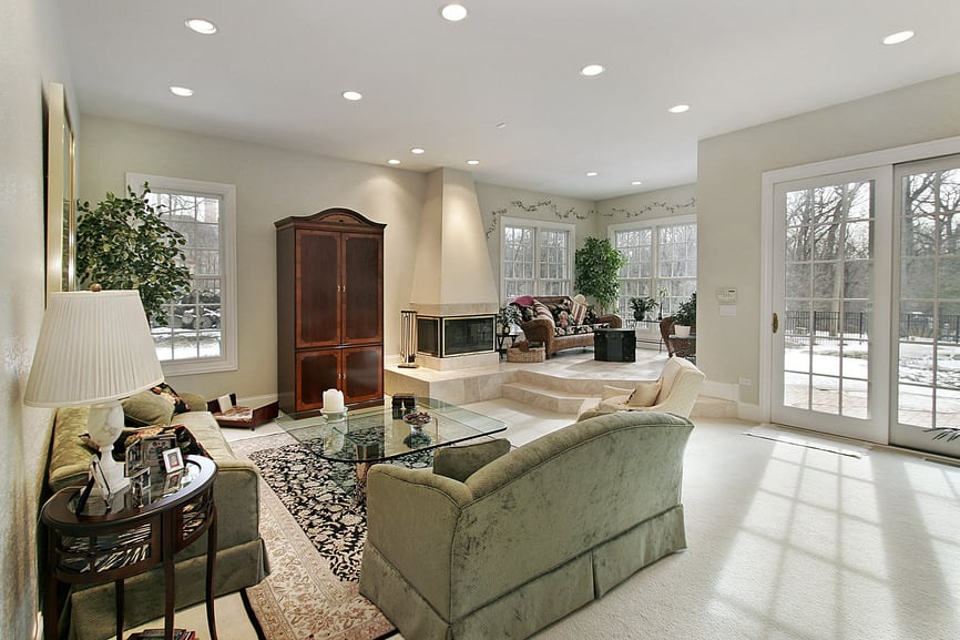 Large living room featuring elegant seats and a glass top center table set on a stylish area rug on top of the carpeted flooring.