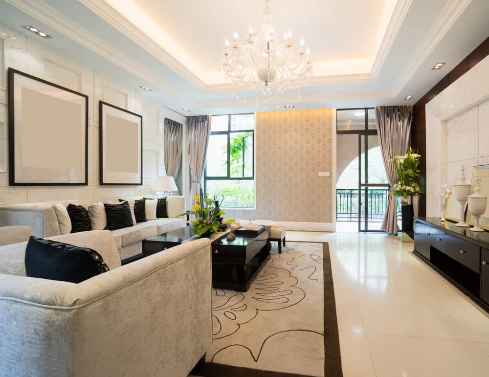 A large living space with a lovely bright tray ceiling lighted by a glamorous chandelier. The area has a cozy sofa set and a modish center table set on top of a stylish area rug covering the tiles flooring.