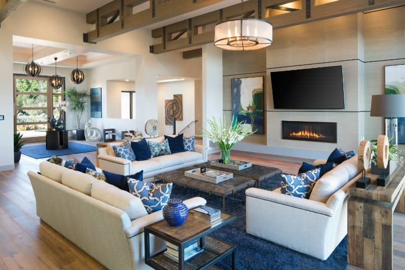 Large family living space featuring a set of white couches and two rustic center tables on top of a blue area rug. The area has a gas fireplace and a large flat-screen TV on the wall.