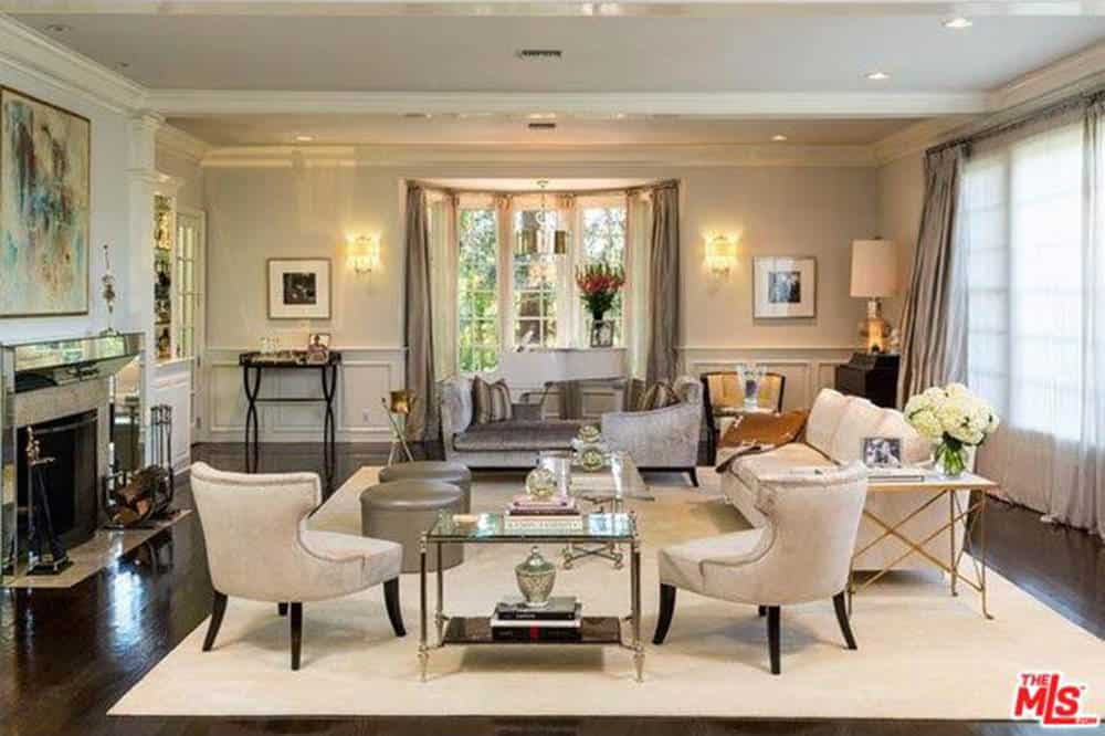 Large formal living room featuring a set of classy pieces of furniture. The area has a white area rug and a fireplace.
