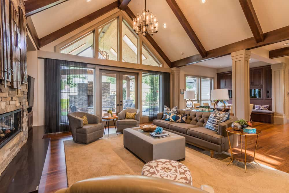 Large formal living room with a tall vaulted ceiling with beams lighted by a fancy chandelier. The room has a modern gray sofa set and a fireplace.