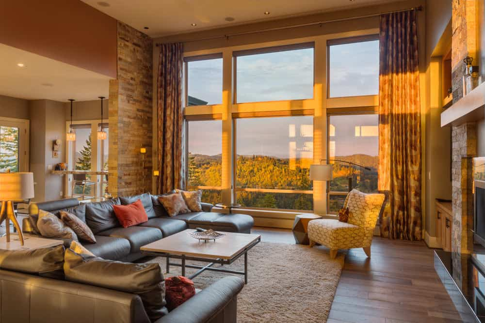 Large modern living space with a large gray sofa set and an area rug covering the hardwood flooring. The large glass windows overlook the stunning outdoor view.