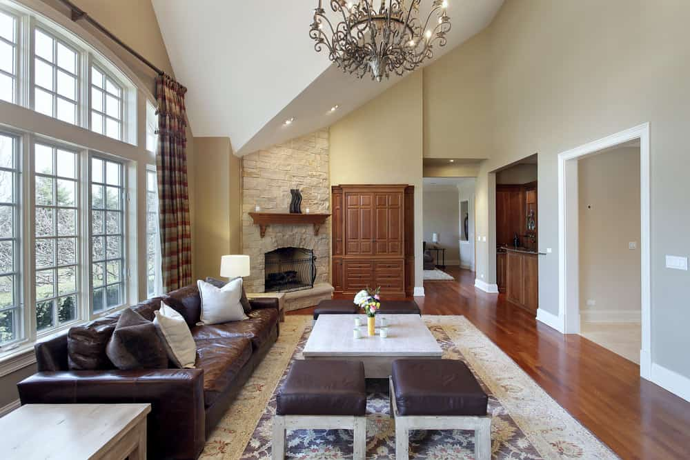 Spacious living space featuring a leather sofa set and a large area rug lighted by a glamorous chandelier.