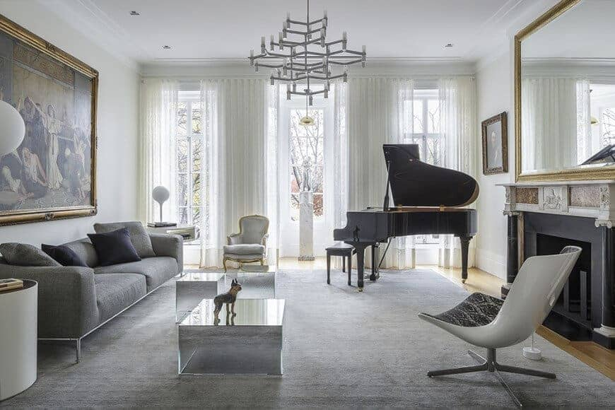 Large formal living room boasting a grand piano on the side, an elegant fireplace, a modern sofa set and a very attractive large wall decor.