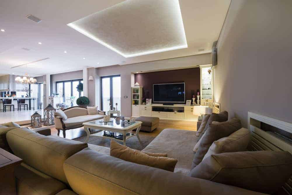 A great room boasting a large living space with a luxurious sofa set and a classy center table situated under the area's gorgeous tray ceiling. There's a large widescreen TV set in front of the space as well.
