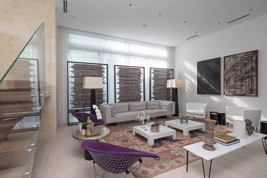 A living space featuring a modern sofa set and a pair of white center tables, lighted by floor lamps.