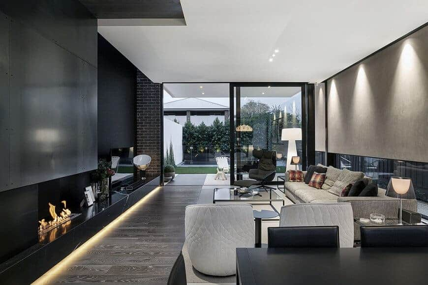 Modern living room featuring a modish fireplace and a flat-screen TV set in front of the handsome-looking sofa set.