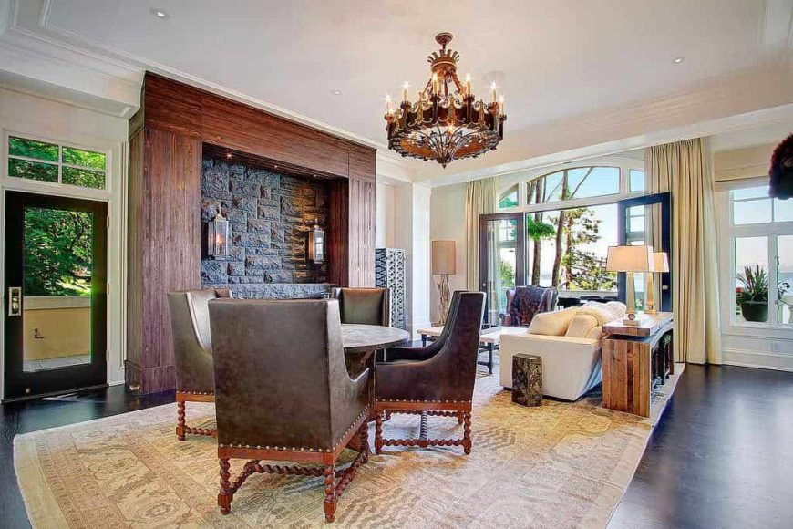 Large formal living room boasting a nice sofa set and a round dining nook with elegant chairs lighted by a stunning chandelier.