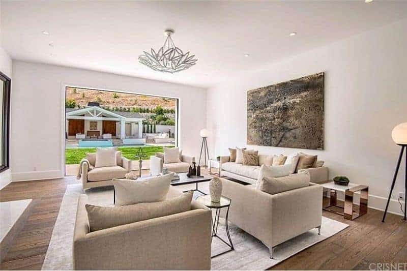 Large formal living room with white walls and hardwood flooring. The room has a cozy sofa set lighted by a fancy ceiling light.
