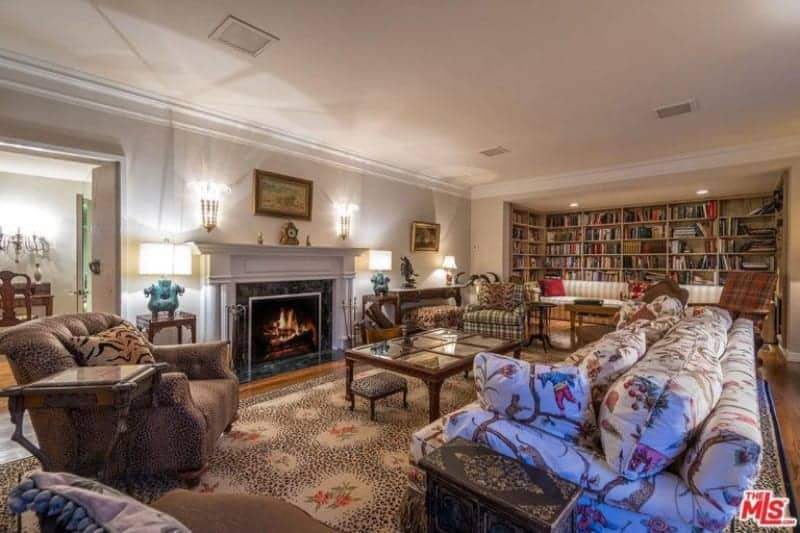 Huge formal living room featuring a set of elegant seats and a fireplace. There's a library area as well with a long couch and large multiple shelving.