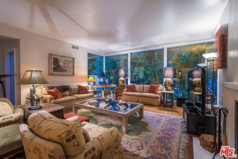 Large family living room featuring classy seats and a large area rug. The room also has a large widescreen TV and a fireplace too.