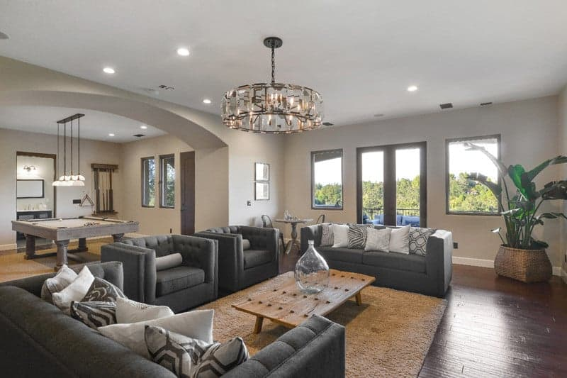 This living room features a dark gray sofa set lighted by a fancy ceiling light. The home has hardwood floors and glass windows.