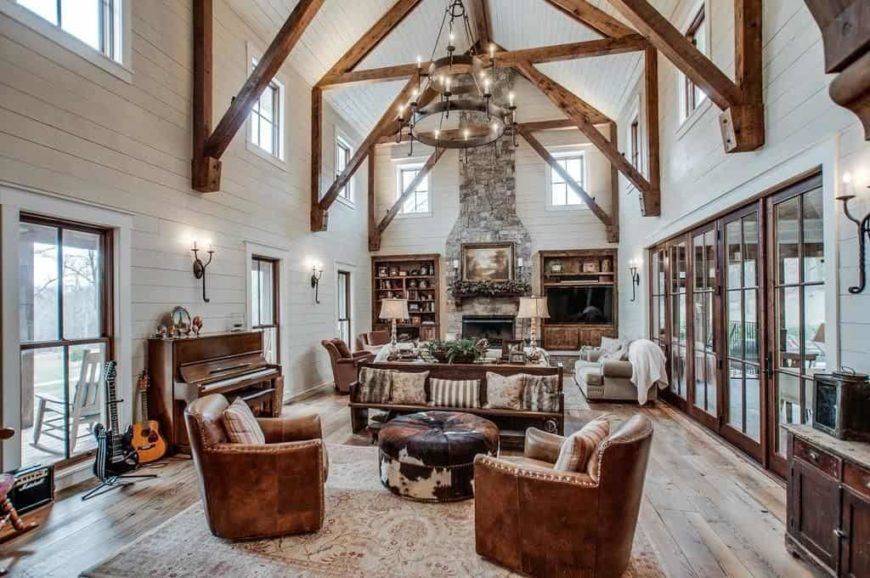 Huge living room featuring hardwood flooring and a tall vaulted ceiling with exposed beams. The room offers elegant seats and other pieces of furniture.