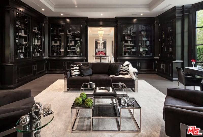 Large formal living room boasting a black and white color scheme. The room offers modern set of seats and an office desk on the side.