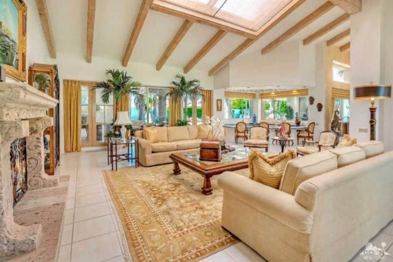 Huge formal living room featuring two classy couches and a center table set just below the skylights. The home also boasts a large elegant fireplace.
