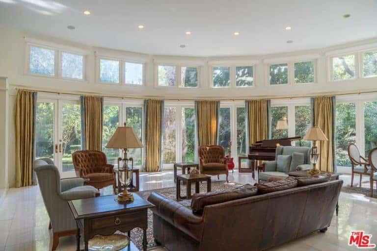 Large formal living room with elegant seats and a classy piano on the side, surrounded by glass windows.