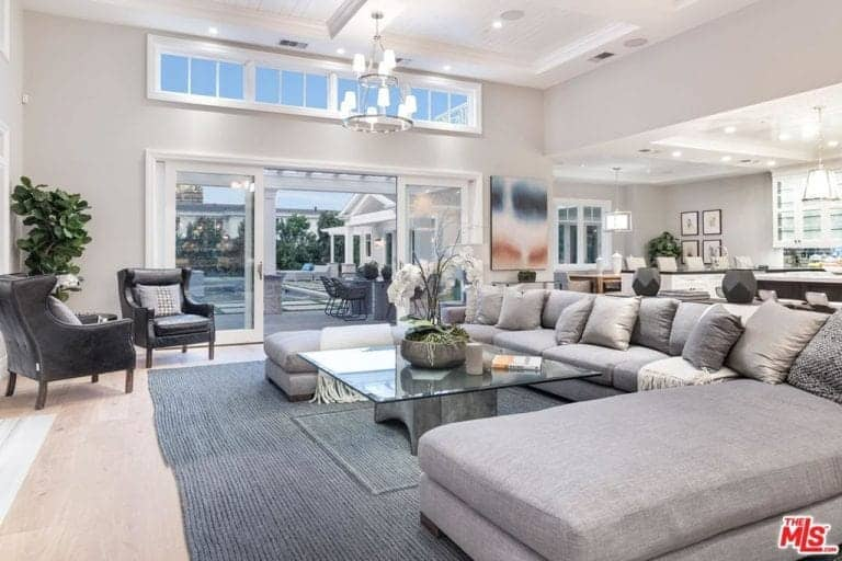 Huge family living room boasting a large U-shaped gray sofa set with a stylish glass top center table and is lighted by a gorgeous ceiling light hanging from the tall ceiling.